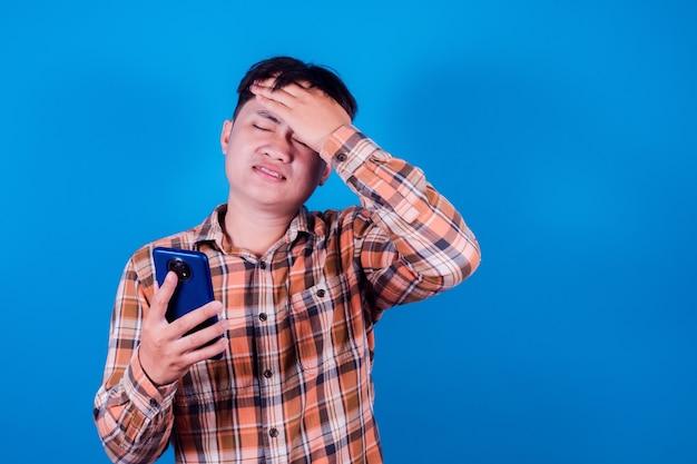 Asiatischer mann trägt ein gestreiftes hemd und sieht traurig aus über die nachrichten, die er auf seinem smartphone erhalten hat