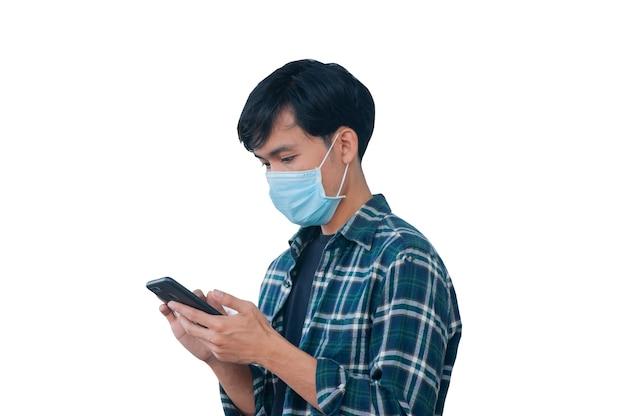 Asiatischer mann trägt gesichtsmaske, schützt covid19 und verwendet den weißen hintergrund des smartphones