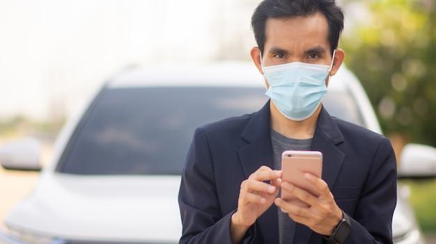 Asiatischer mann trägt gesichtsmaske zum schutz des ausbruchs des covid19-coronavirus, mann, der smartphone-handel mit börsenlebensstil im freien verwendet
