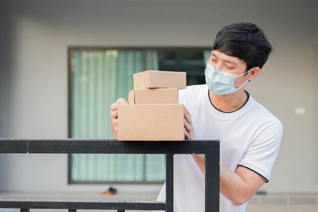 Asiatischer mann trägt maske und steht vor haus, um bestellung von der lieferung zu erhalten