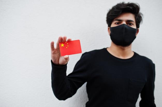 Asiatischer mann tragen ganz schwarz mit gesichtsmaske halten china-flagge in der hand lokalisiert auf weiß. coronavirus-länderkonzept.