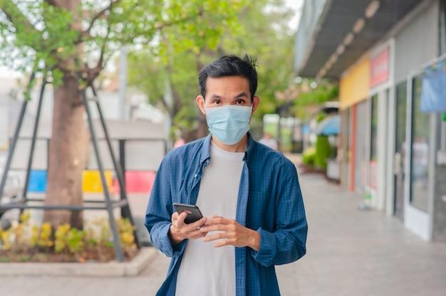 Asiatischer mann tragen medizinische maske unter verwendung des smartphones, das auf straße geht