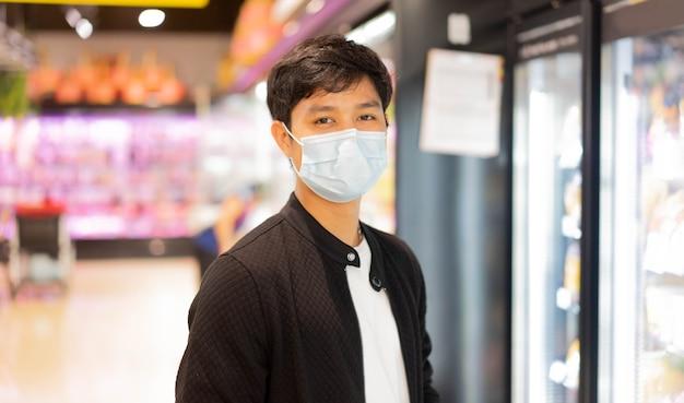 Asiatischer mann tragen schützende gesichtsmaske beim einkaufen im supermarkt für neues normales lebensstilkonzept