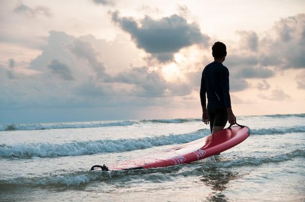 Asiatischer mann tragen surfbrett am strand