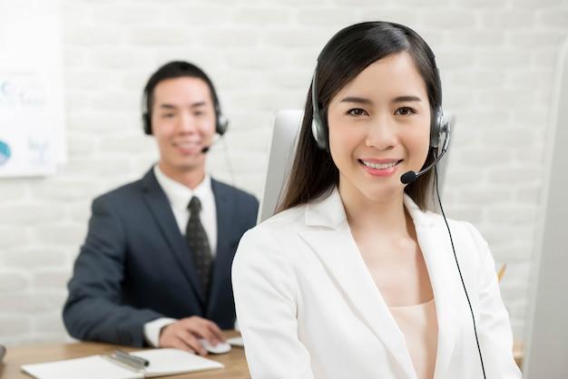 Asiatischer mann und asiatische frau, die in einem kundenkontaktcenter arbeiten