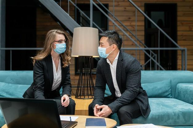 Asiatischer mann und eine frau mit medizinischen schutzmasken sitzen im büro am computer