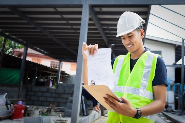 Asiatischer mann und frau bauingenieur papierplan gebäudearchitekt tragen weißen sicherheitshelm blick auf baustelle.