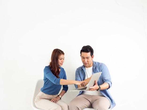 Asiatischer mann und frau, die mit laptop-computer für geschäft auf weißem hintergrund spricht