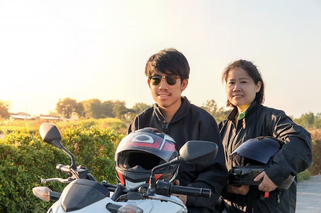 Asiatischer mann und frau mit sturzhelm und tragen und befestigen, bevor sie großes fahrradmotorrad auf die straße zur sicherheit reiten