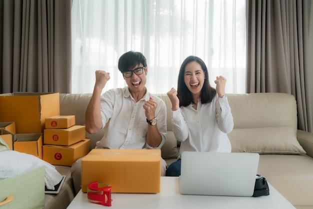 Asiatischer mann und frau verkaufen ihre online über den computer im haus und sind sehr zufrieden, wenn es viele ihrer bestellungen gibt. kmu-unternehmer oder freiberuflich tätiges unternehmenskonzept