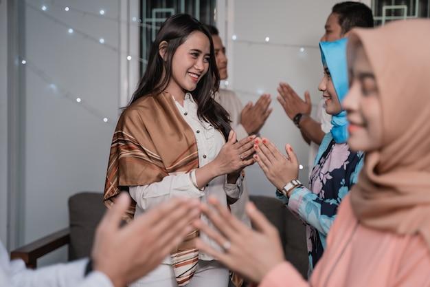 Asiatischer mann und hijab-frau begrüßen sich entschuldigend