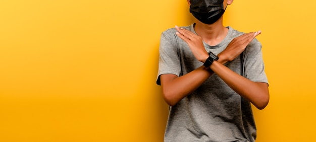 Asiatischer mann verhindert coronavirus covid-19. mann mit schwarzer maske. verhindern sie infektionen atemwegserkrankungen virusschutzkonzept gelber hintergrund Premium Fotos