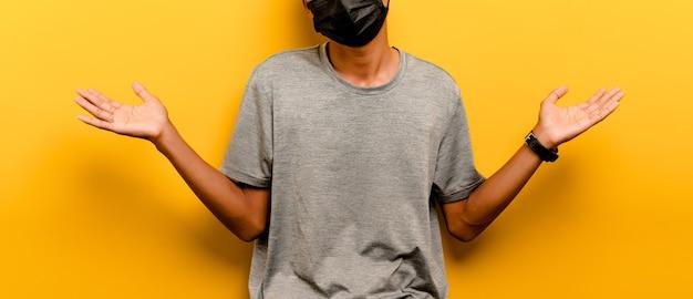 Asiatischer mann verhindert coronavirus covid-19. mann mit schwarzer maske. verhindern sie infektionen atemwegserkrankungen virusschutzkonzept gelber hintergrund