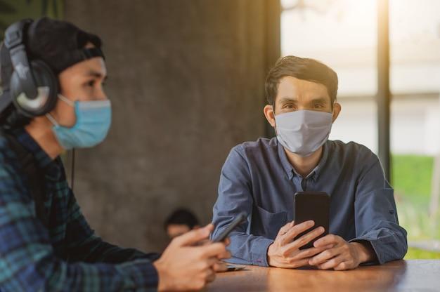 Asiatischer mann verwenden handy im café innen eine tragende gesichtsmaske schützen corona-virus neuen normalen lebensstil