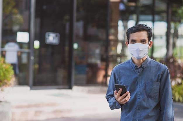 Asiatischer mann verwenden handy tragen gesichtsmaske outdoor-lebensstil neue normalität