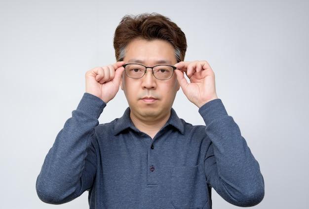 Asiatischer mann von mittlerem alter, der versucht, gläser auszuziehen und etwas zu sehen. schlechte sicht, presbyopie, myopie.