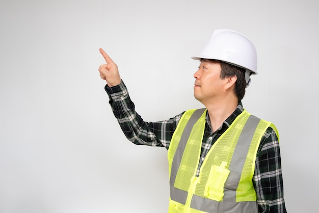 Asiatischer mann von mittlerem alter in einer hellgrünen arbeitsweste und in einem weißen sicherheitshut.