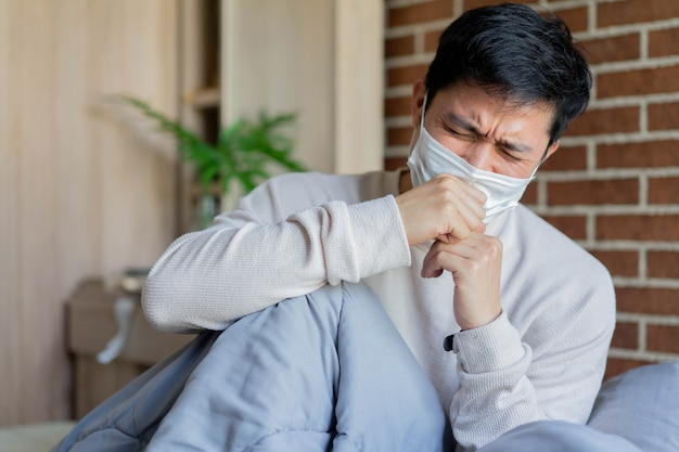 Asiatischer mann wacht auf und hustet im schlafzimmer (quarantänebereich) zur vorbeugung von coronaviren