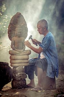 Asiatischer mann wird stein in ein buddha-bild ayutthaya thailand geschnitzt