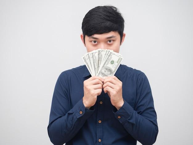 Asiatischer mann zeigt geld, schließt sein gesicht auf weißem hintergrund, geschäftsmann schließt sein gesicht mit dollargeld