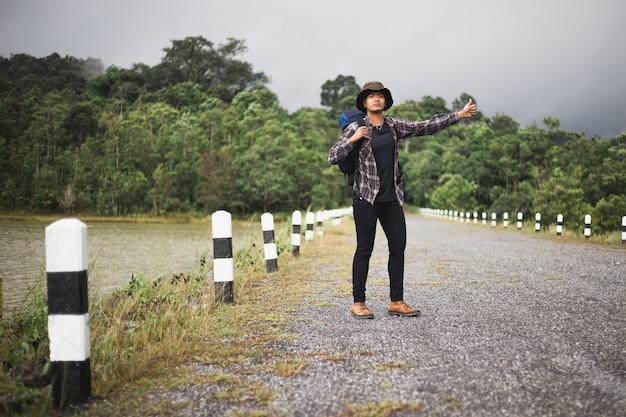 Asiatischer mann zeigt seine hände, um hilfe von einem auto zu suchen, das durch fuhr