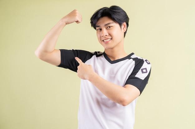 Asiatischer mann zeigt seine muskeln