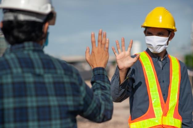 Asiatischer mann zwei personen ingenieur schütteln hand neue normalität vor ort bau