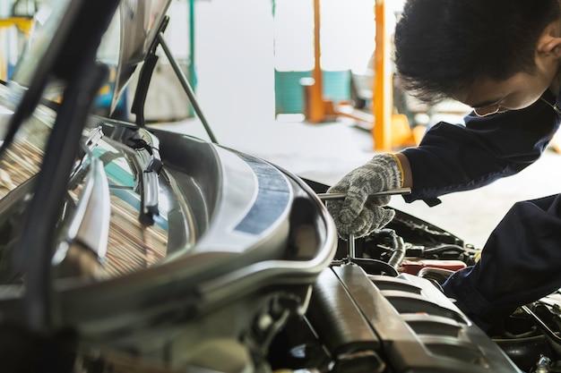 Asiatischer mannautomechaniker, der einen schlüssel verwendet, um auto in der garage instandzuhalten.