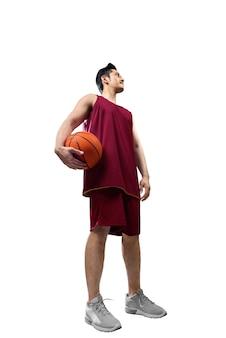 Asiatischer mannbasketballspieler, der die kugel anhält