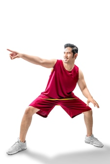 Asiatischer mannbasketballspieler in der haltung des tröpfelns der kugel