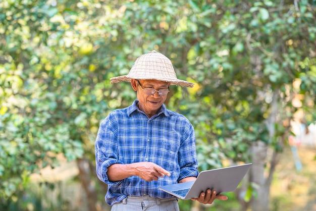 Asiatischer mannbauer mit geschäfts- und technologiekonzept des smartphones und des laptops, asiatischer mannbauer auf leerem kopienraum