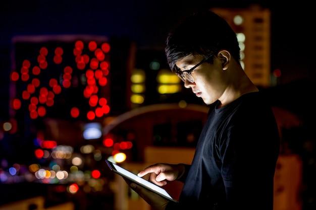 Asiatischer mannblick der gläser auf seine computertablette während der nacht mit stadtlichtern. konzentriere dich auf seine hand. geringe schärfentiefe.