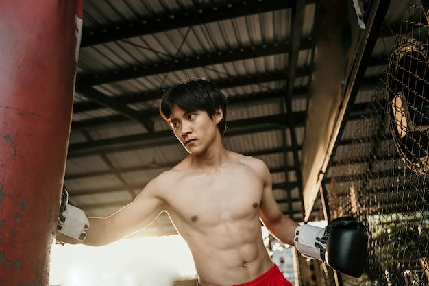 Asiatischer mannboxer während des boxens, der schwere tasche am trainingsfitness-fitnessstudio schlägt