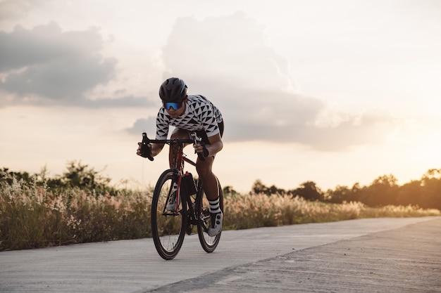Asiatischer mannfahrrad am sonnensatz. das bild des radfahrers in der bewegung auf dem hintergrund