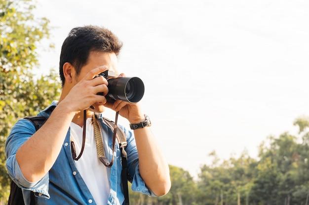 Asiatischer mannfotograf, der bild mit kamera im freien am park, freiberufler oder freizeitaktivitätskonzept fotografiert