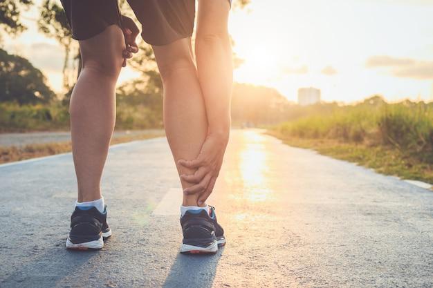 Asiatischer manngebrauchshände halten an seinen knöchel beim laufen auf straße im park
