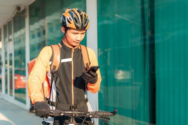 Asiatischer mannkurier, der kundenadresse in karte im smartphone auf fahrrad überprüft, das lebensmittel liefert
