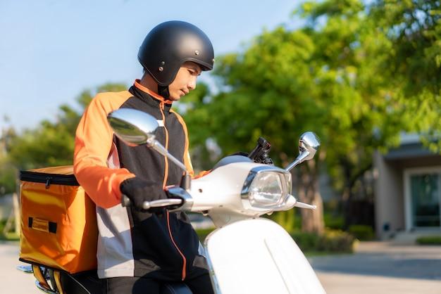 Asiatischer mannkurier, der kundenstandort in der karte im smartphone auf roller überprüft, der lebensmittel liefert