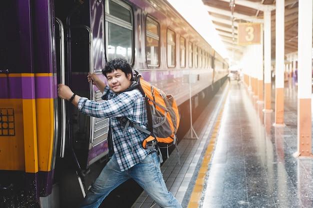 Asiatischer mannreisender mit rucksack verstärkt den zug in der bahnstation.