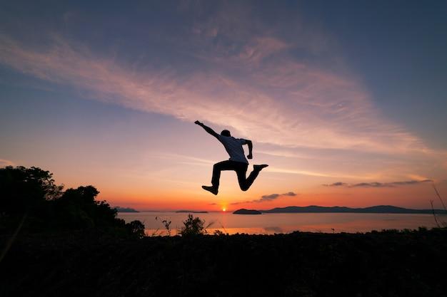 Asiatischer mannreisender springt auf einen regenwaldberg