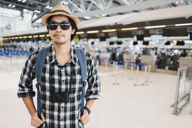 Asiatischer manntaschen-satztourist mit kamera im flughafen.