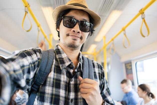 Asiatischer manntaschenpackungstourist nehmen ein selfie in einem zug.