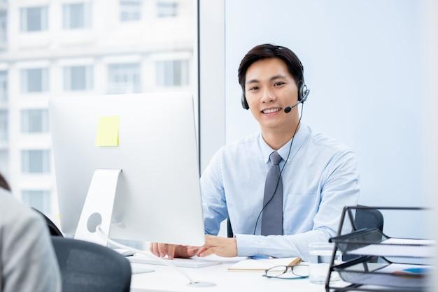 Asiatischer manntelemarketer, der im büro arbeitet
