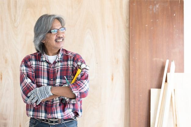 Asiatischer manntischler, der an holzbearbeitungstabelle in der hauptzimmerei arbeitet