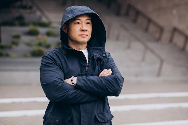 Asiatischer manntourist, der außerhalb der straße geht