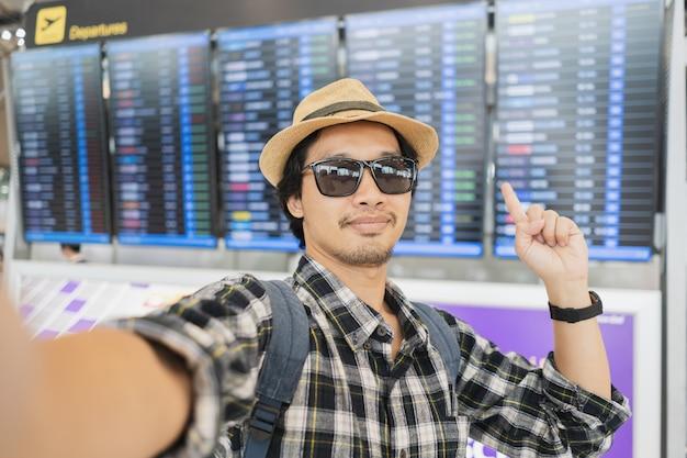 Asiatischer manntourist, der ein selfie mit intelligenter telefonkamera im flughafen nimmt.