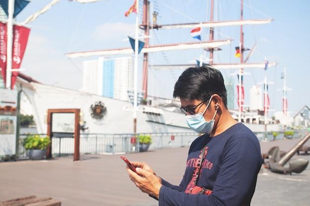 Asiatischer manntourist, der gesichtsmaske mit handy am bangkok-reisestandort trägt
