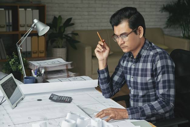 Asiatischer mannzeichnungsplan in seinem gemütlichen büro