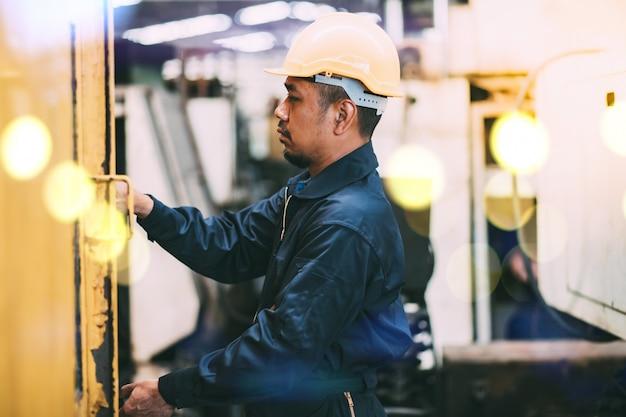 Asiatischer maschinenbau in sicherheit mechanikeranzug und schutzhelm stehen arme gekreuzt in lkw und gabelstapler wartungsgarage.
