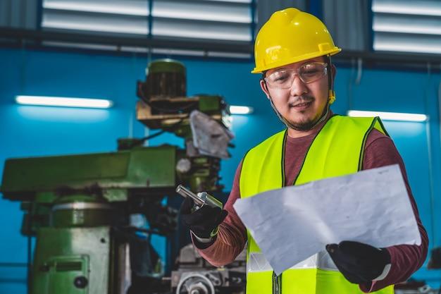 Asiatischer maschinist im sicherheitsanzug, der das teil der ausrüstung mit spezifikationspapier überprüft